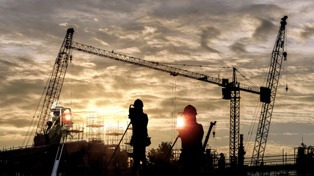 Double exposure of silhouette black man survey and civil engineer stand on ground working in a land building site over Blurred construction worker on construction site. examination, inspection, survey