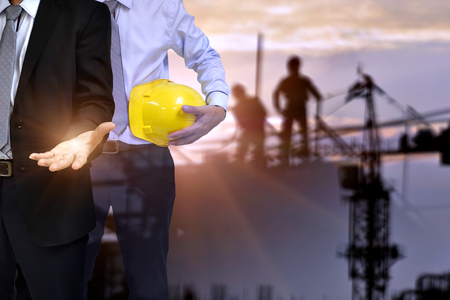 Construction concept .Double exposure of success businessman show his hand to success concept and  engineer  holding helmet , blur construction background . Occupational health and safety . Stock Photo