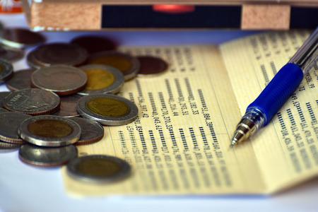 Baht coins, deposit accounts, pen, concept of saving money.