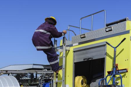 Fireman climbing down from the Fire truck .