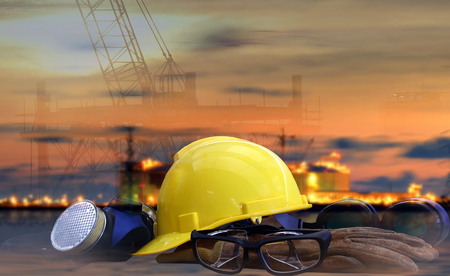 Safety in Refinery Concept , safety standard set  on working table, Background power plant , heavy petrochemical industry estate use for energy , power , fuel ,gas and fossil petroleum topic.