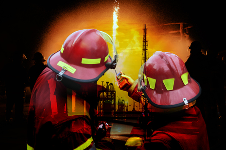Emergency rescue fireman team to firefighter at oil refinery plant .