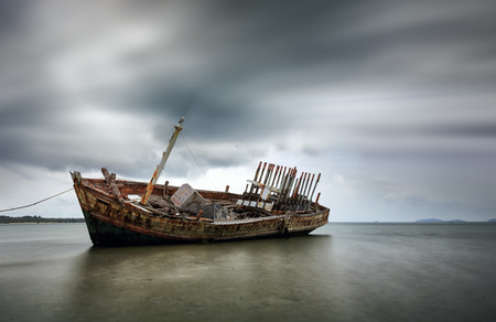 An old shipwreck or abandoned shipwreck. , Wrecked boat abandoned stand on beach or Shipwrecked off the coast of Thailand. Stock Photo