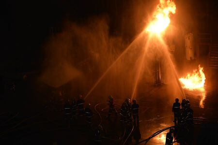 Firemen fighting a raging fire with huge flames of burning timber.Background for rescue ,emergency concept . Editorial