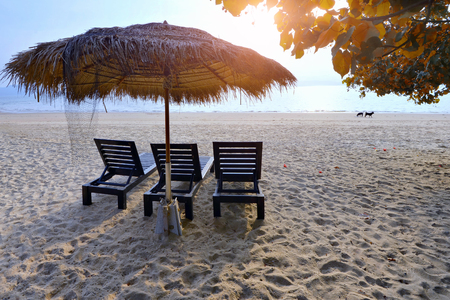 Vacation holidays background wallpaper - three beach lounge chairs under tent on beach .