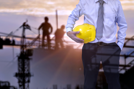 Engineer or Safety officer holding hard hat with the mobile crane machine is background in construction site.