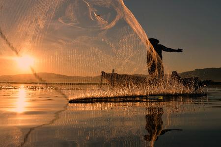 Fisherman  of  Bangpra  Lake in action when fishing, Chonburi, Thailand.