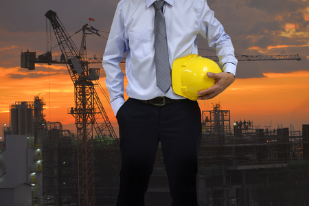 Safety Construction Concept , Safety engineer holding yellow hardhat and construction sunset background.