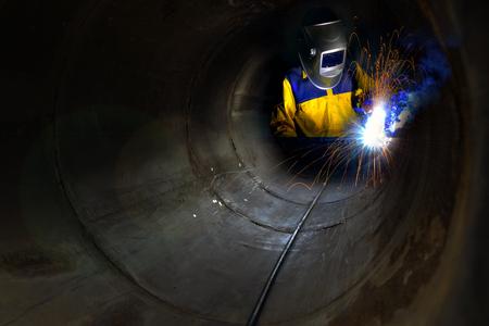 산업 노동자, 용접 금속 및 많은 날카로운 스파이크 제한 된 공간 건설 배관 내부. 스톡 콘텐츠