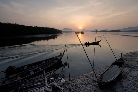 Silhouettes of the traditional stilt fishermen at sunrise , Phang Nga Thailand .Slow life in Thailand .