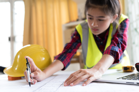 Professional safety engineer , young Asian female  working at her office  wears safety equipment and safety standard on working table . Concept for construction safety .