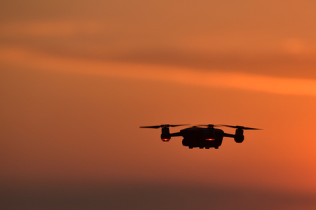 Drone flying in the sunset . The drone with the professional camera takes pictures.