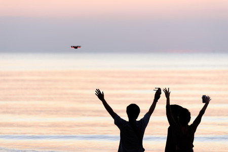 Silhouette of young group  using drone at sunset beach for photos .