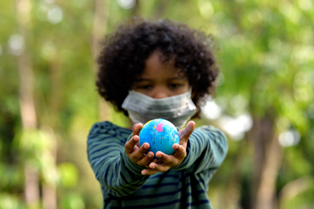 Mixed race boy holding Earth in hands against green background , Ecology concept.