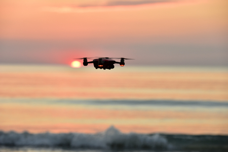 Drone flying in the sunset at beach  .The drone with the professional camera takes pictures.
