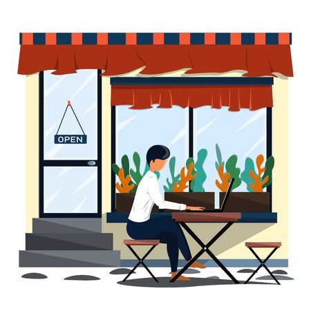 A man sits on the street at a table in a cafe and works on a laptop.