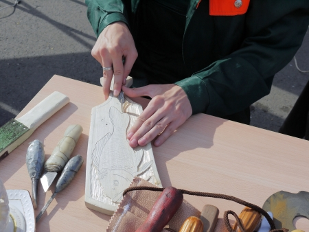 SARATOV, RUSSIA - SEPTEMBER 15 2012: The Hands of an unknown Woodcarver cuts out a picture of a fish on the wood on the exhibition dedicated to the districts of the Saratov region. Stock Photo - 15269847