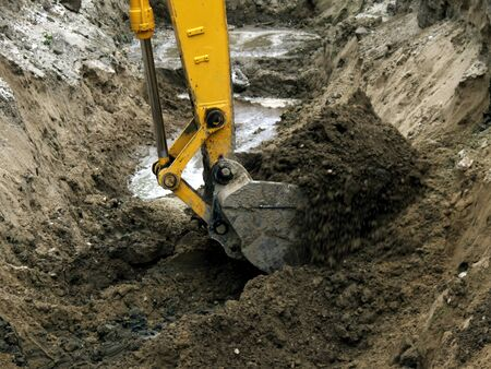 Photo of the bucket of the excavator digging the pit.