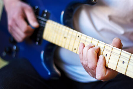 Man playing a guitar, focus on the hand holding the fretboard  Stock Photo