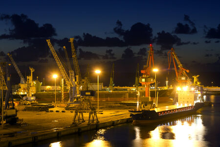 sea seaport: View on seaport with cranes at the night. Stock Photo