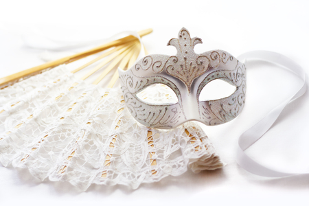 White mask for carnival and fan on white background