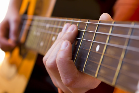 kid playing a guitar, focus on the hand holding the fretboard Stock Photo