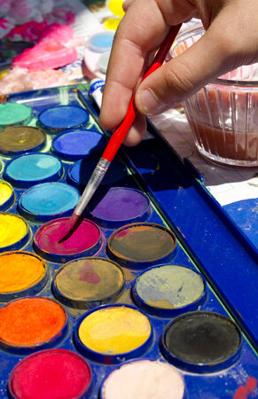 mingle: Hand of the artist drawing water colour paints