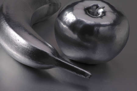 luster: A chrome banana and apple on a silver background.