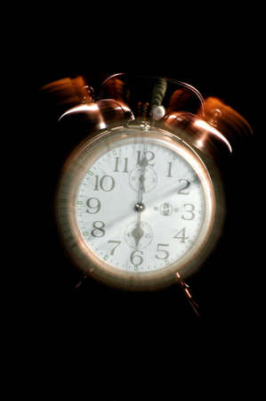 An old-fashioned alarm clock set to 6 a.m. The clock appears to be ringing. Фото со стока