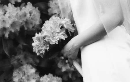 A black and white photo of a brides hands holding a bouquet in front of a background of flowers.