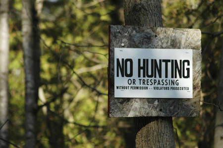 trespass: keep out, sign, restrictions, restrict, forbid, forbidden, irony, humor, tree, trees, forest, trespass, trespassing Stock Photo