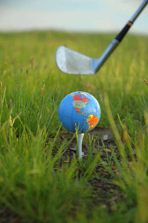 A miniature globe on a tee at a golf course. A golf club is poised behind the globe ready to swing.