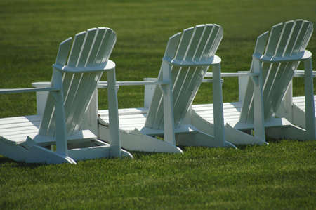 vividly: A row of three white, wooden  lawn chairs on a vividly green lawn. Stock Photo