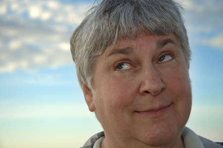 A gray-haired woman rolls her eyes.