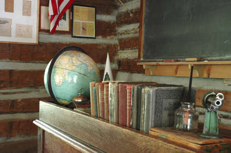 schoolhouse: A teachers desk and a chalkboard in an old-fashioned one-room schoolhouse. Stock Photo