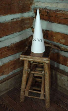 schoolhouse: A dunce cap sitting on a stool in the corner of an old schoolhouse.