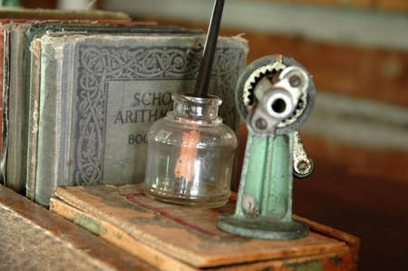 Objects on a teachers desk in a one-room schoolhouse, including tattered books, an old pencil sharpener, and an ink well.