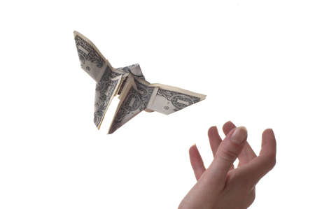 A hand trying to catch a dollar shaped like a butterfly. The background is white. photo