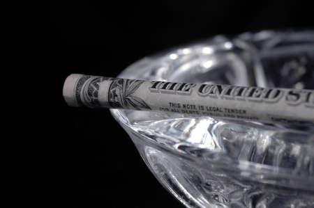 Een dollar vorm van een sigaret die berust op een asbak.