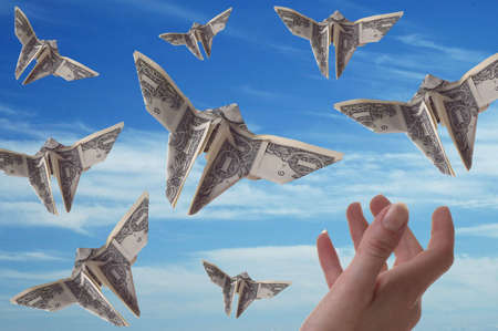 A hand trying to catch dollar bills shaped like butterflies. A blue sky serves as the background.