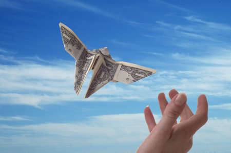 A hand trying to catch a dollar bill shaped like a butterfly. A blue sky serves as the background.