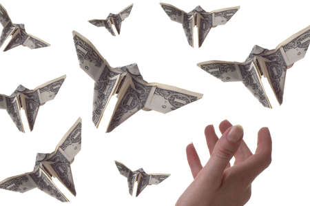 A hand trying to catch dollar bills shaped like butterflies. The background is white. Imagens
