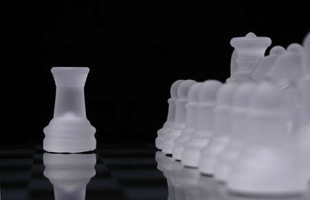 A rook from a glass chess set is out of line with rows of pieces from the same side.