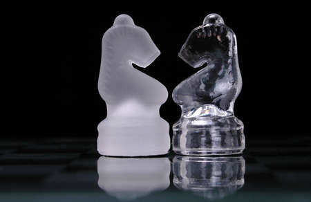 Opposing knights from a glass chess set face off. 版權商用圖片 - 509801