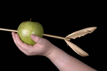 A hand holding a green apple pierced by a golden arrow. Banco de Imagens