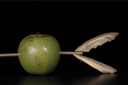 marksmanship: A green apple pierced by a golden arrow agaisnt a black background.