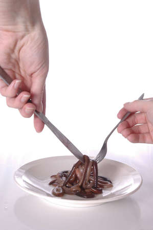revolting: Hands holding a knife and a fork above a plate of worms. Stock Photo