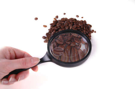 A pile of coffee beans under a magnifying glass.