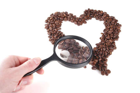 A heart made from coffee beans. Some of the coffee beans are under a magnifying glass. White background.