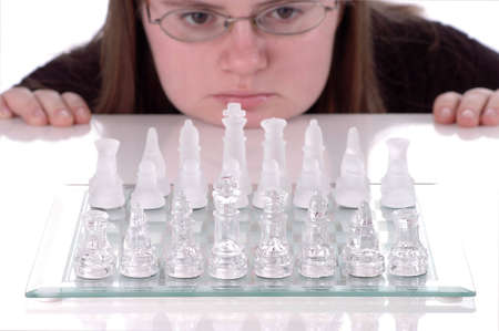 strategizing: A woman rests her chin against a table and stares at a chess board as she ponders her next move. Stock Photo